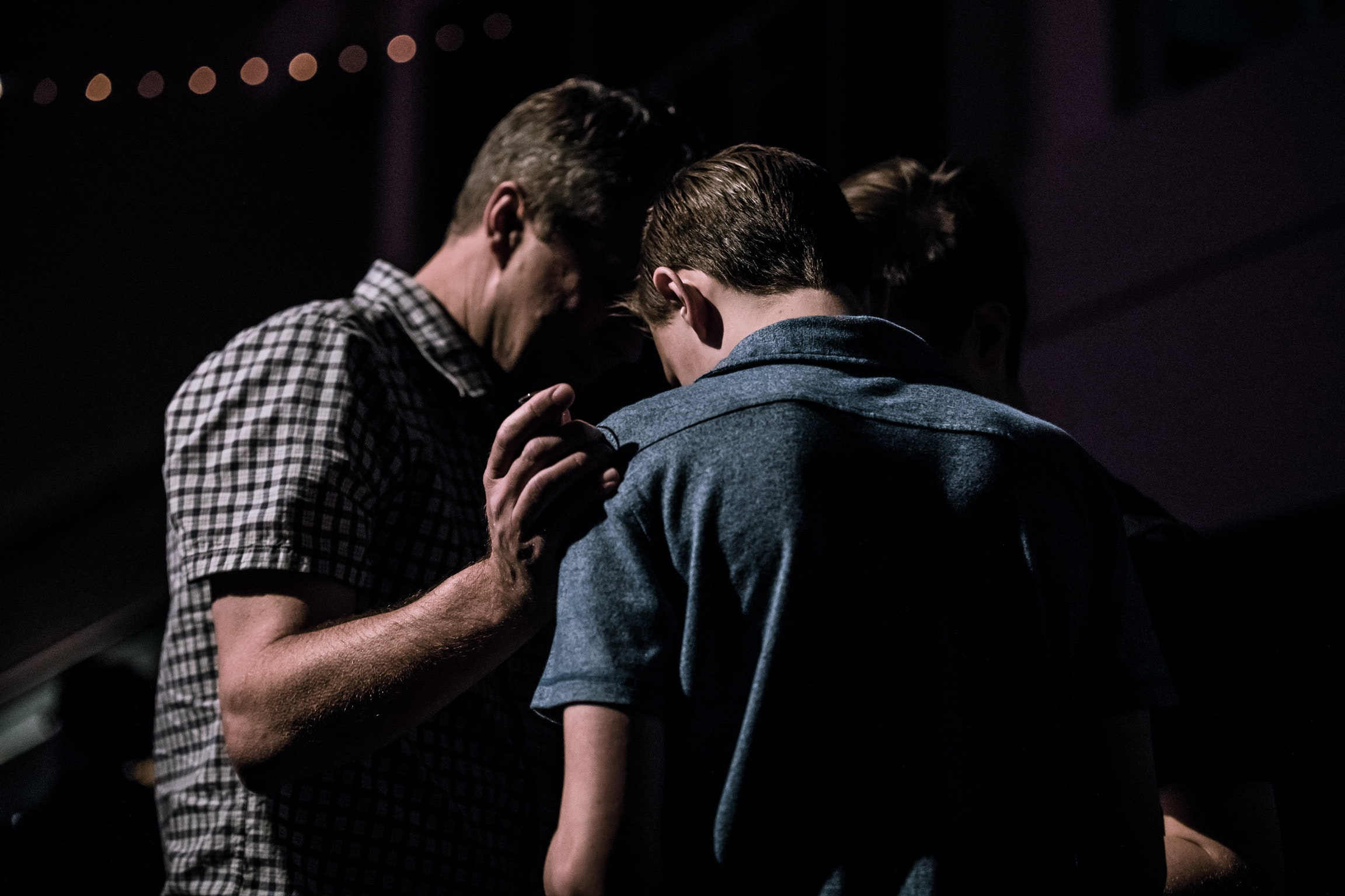 youth pastor praying for student