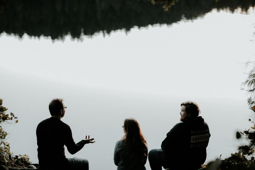 YWAMers talking together beside a lake