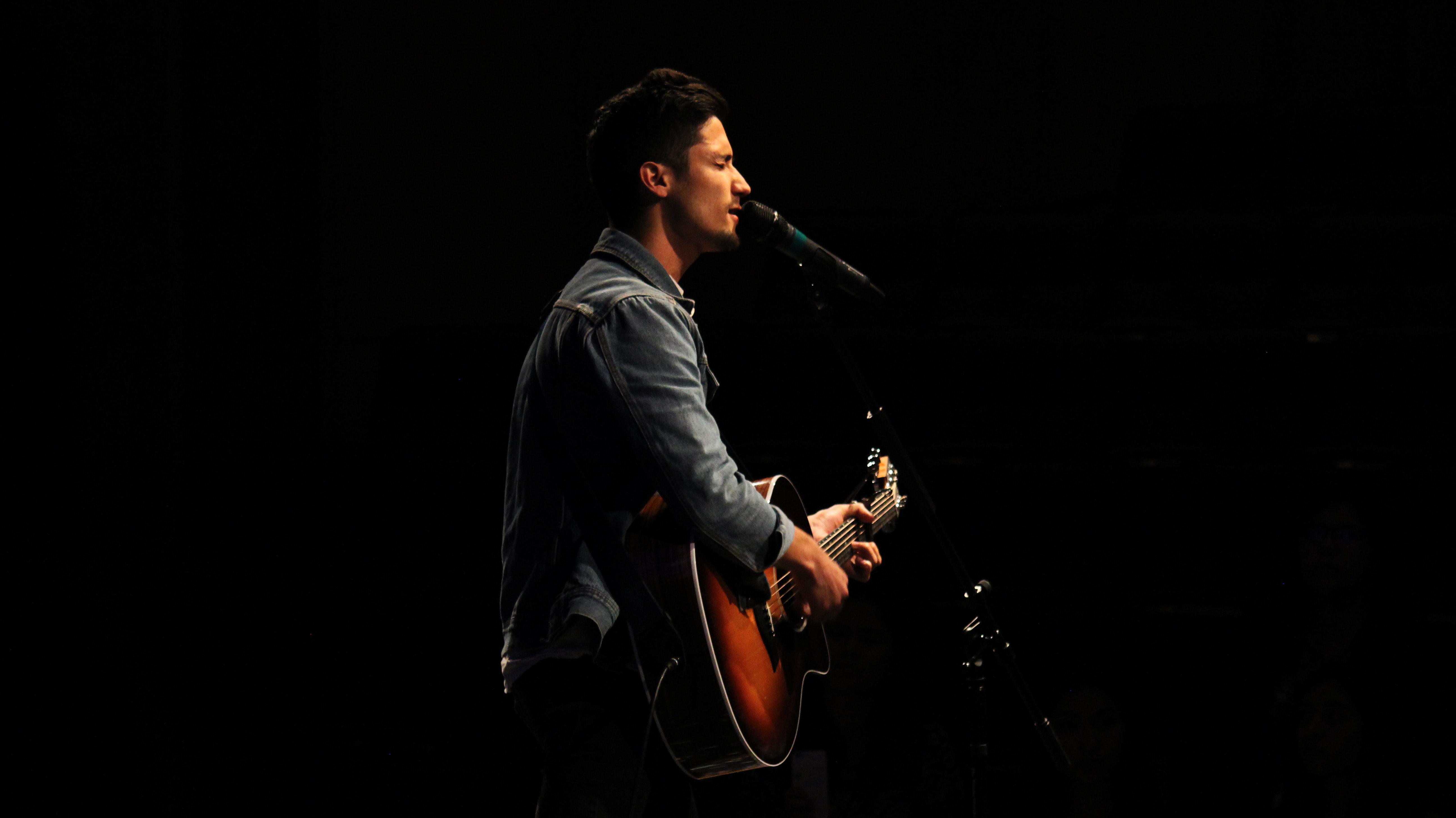 YWAMer playing guitar and singing